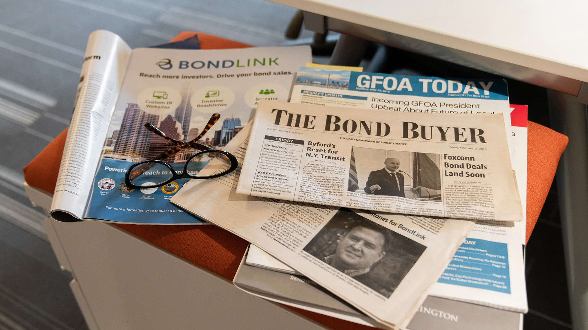 Stack of newspapers and magazines featuring BondLink
